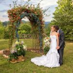 Bride and groom in front of an arbor